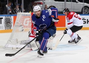 PRAGUE, CZECH REPUBLIC - MAY 5: France's Yorick Treille #7 plays the puck in the Austrian zone while Mario Fischer #50 lookS on during preliminary round action at the 2015 IIHF Ice Hockey World Championship. (Photo by Andre Ringuette/HHOF-IIHF Images)