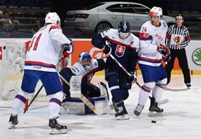 OSTRAVA, CZECH REPUBLIC - MAY 6: Norway's Andreas Martinsen #24 and Slovakia's Juraj Mikus #26 battle for a loose puck in front of Slovakia's Jan Laco #50 during preliminary round action at the 2015 IIHF Ice Hockey World Championship. (Photo by Richard Wolowicz/HHOF-IIHF Images)