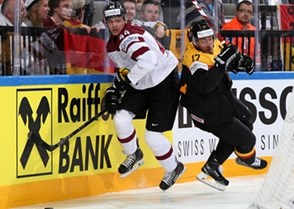 PRAGUE, CZECH REPUBLIC - MAY 8: Germany's Marcus Kink #17 and Latvia's Oskars Cibulskis #44 battle for the puck behind the Latvian goal during preliminary round action at the 2015 IIHF Ice Hockey World Championship. (Photo by Andre Ringuette/HHOF-IIHF Images)