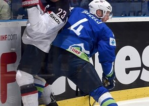 OSTRAVA, CZECH REPUBLIC - MAY 10: Slovenia's Andrej Tavzelj #4 collides with USA's Matt Hendricks #23 along the boards during preliminary round action at the 2015 IIHF Ice Hockey World Championship. (Photo by Richard Wolowicz/HHOF-IIHF Images)