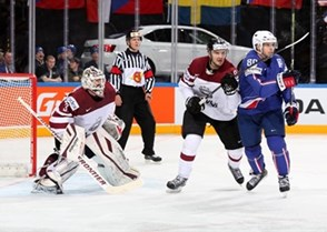 PRAGUE, CZECH REPUBLIC - MAY 12: Latvia's Edgars Maslaskis #31 looks on as teammate Krisjanis Redlihs #9 battles with France's Teddy da Costa #80 during preliminary round action at the 2015 IIHF Ice Hockey World Championship. (Photo by Andre Ringuette/HHOF-IIHF Images)